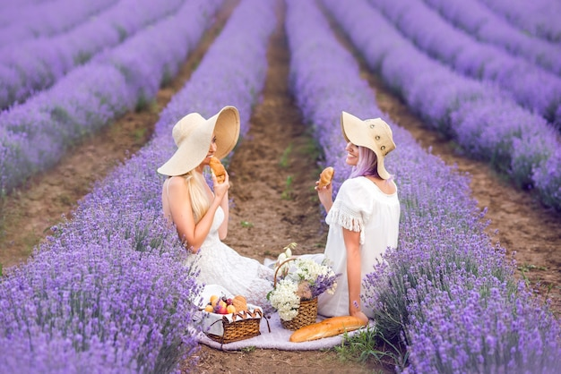 Dziewczyny w czapkach i białej sukni siedzą na lawendowym polu. piknik w lawendzie. rogaliki i bułeczki w dłoni.