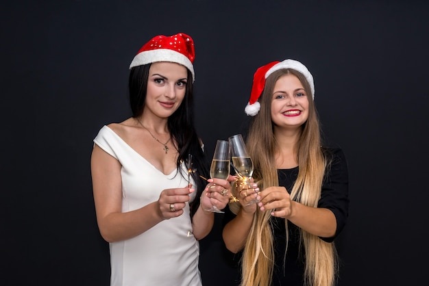 Dziewczyny w czapkach mikołaja i szampanie z bengalskimi światłami