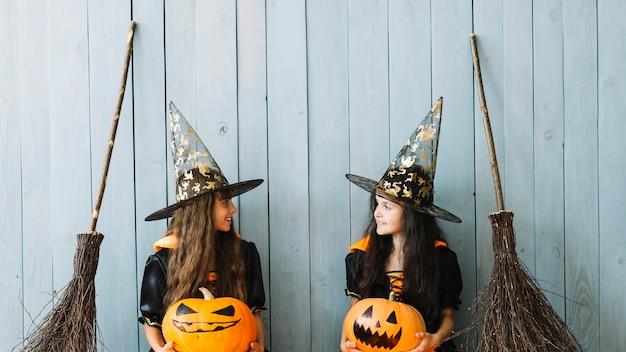 Dziewczyny w czarownicach garnitury gospodarstwa pomarańczowe dynie i patrząc na siebie