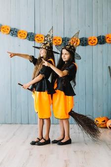 Dziewczyny w czarownicach garnitury siedzi na miotle, wskazując od hotelu