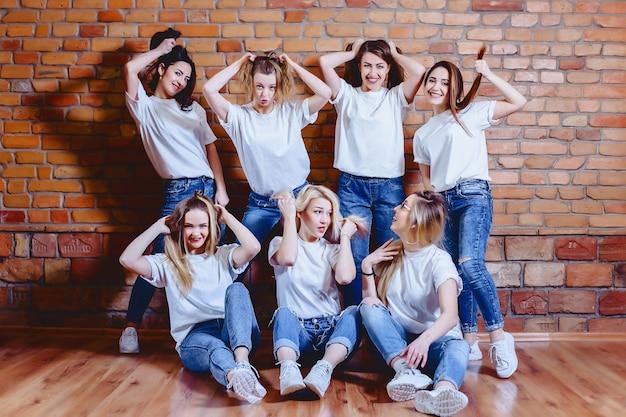 Dziewczyny w dżinsach przy tłem ściana z cegieł