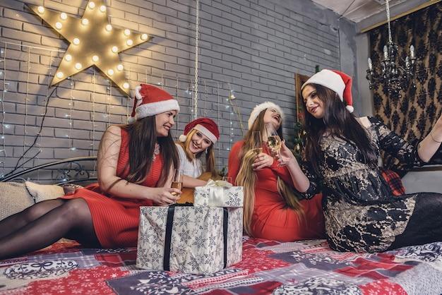 Dziewczyny w eleganckich sukienkach pozują w świątecznej pracowni