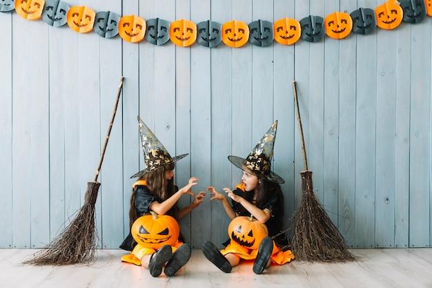 Dziewczyny w kostiumach czarownic wykonujących przerażające gesty