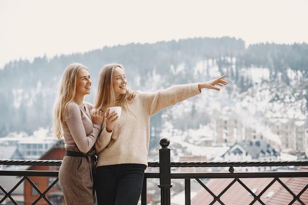 Dziewczyny w lekkich ubraniach. zimowa kawa na balkonie. szczęśliwe kobiety razem.