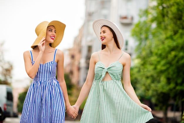 Dziewczyny w letnich sukienkach i słomkowych kapeluszach pozują razem