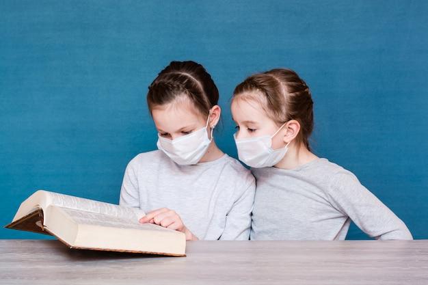 Dziewczyny w maskach medycznych podczas kwarantanny czytają książkę przy stole. edukacja dzieci w izolacji podczas epidemii