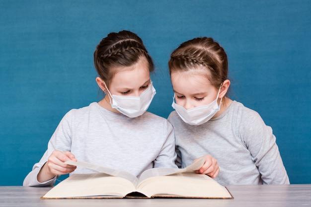 Dziewczyny w maskach medycznych podczas kwarantanny uważnie czytają książkę przy stole. edukacja dzieci w izolacji podczas epidemii