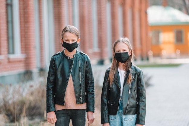 Dziewczyny w maskach na tle nowoczesnego budynku,