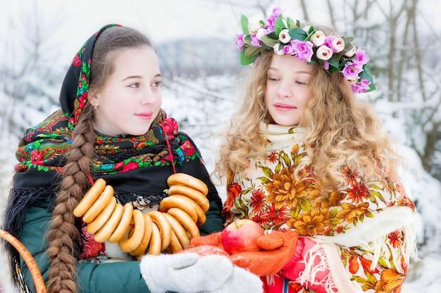Dziewczyny w rosyjskich strojach ludowych w zimowym krajobrazie