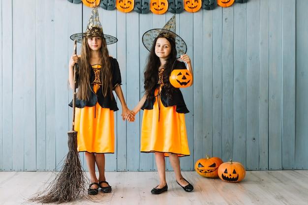Dziewczyny w stroju czarownic stojący z miotłą i trzymając się za ręce