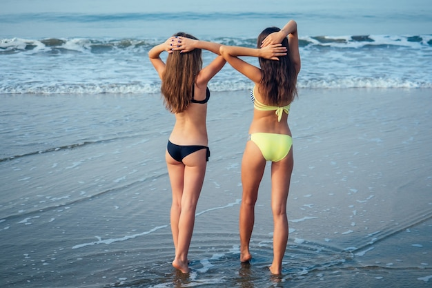 Dziewczyny w stroju kąpielowym na plaży o pięknej figurze
