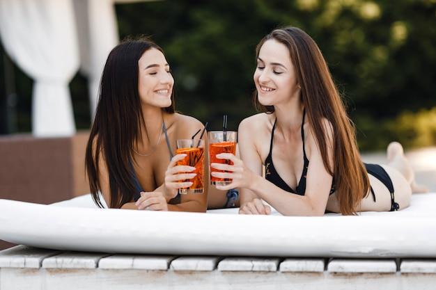 Dziewczyny w stroju kąpielowym opalają się na leżaku