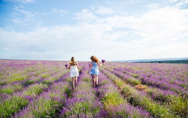 Dziewczyny w sukienkach biegnących przez lawendowe pole