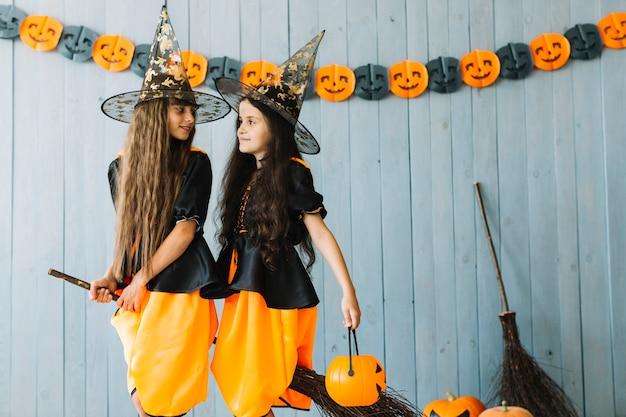 Dziewczyny w szacie czarownic i spiczaste czapki siedzące na miotle