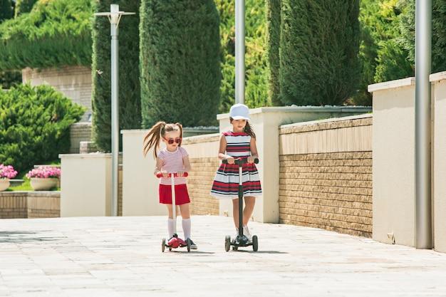 Dziewczyny w wieku przedszkolnym, jazda skuterem na świeżym powietrzu.