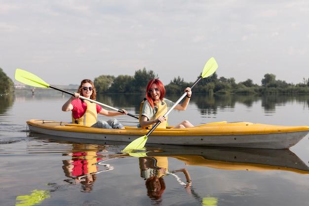 Dziewczyny, wioślarstwo w kajaku na jeziorze