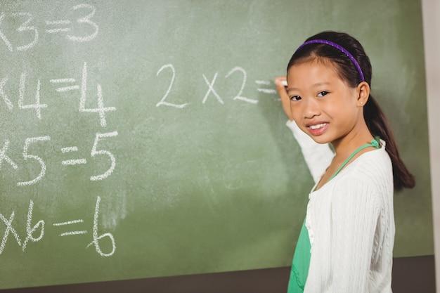 Dziewczyny writing z kredą na blackboard