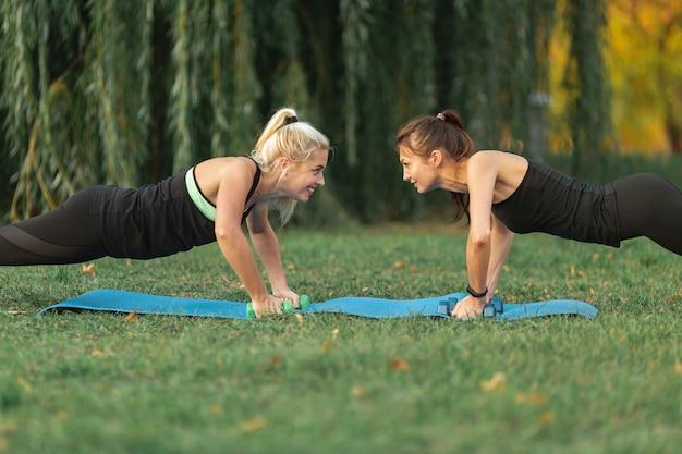 Dziewczyny z boku patrzą na ćwiczenia jogi na zewnątrz