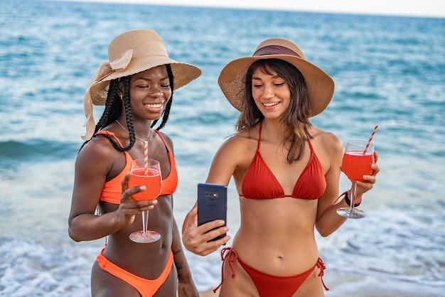 Dziewczyny z koktajlami i smartfonem na plaży