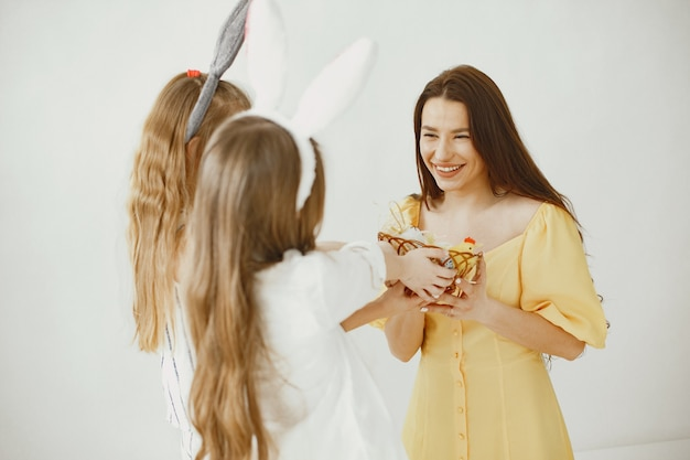 Dziewczyny z koszem jajek. szczęśliwa mama w żółtej sukience. długie włosy u dziewcząt.