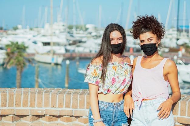 Dziewczyny z maską na twarz pozują w pobliżu portu