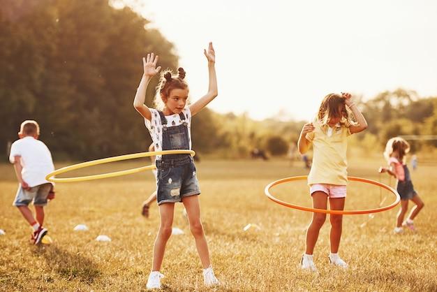 Dziewczyny z narzędziem fitness koło. grupa dzieci ma aktywny weekend w terenie.
