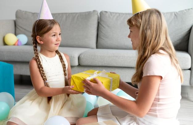 Dziewczyny ze średnim strzałem trzymają prezent