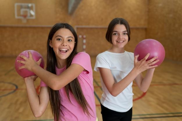 Dziewczyny ze średnim strzałem trzymające piłki holding