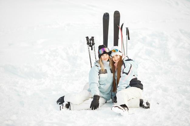 Dziewczyny zostawiły narty na śniegu. dobra zabawa na fotografowaniu. spędzaj czas w górach.