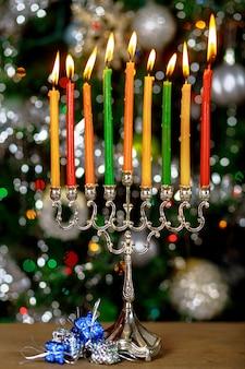 Dziewięć kolorów świec na menorze na kolorowej powierzchni