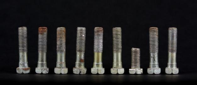 Dziewięć śrub z nakrętkami w rzędzie. jeden obiekt jest wyjątkiem.