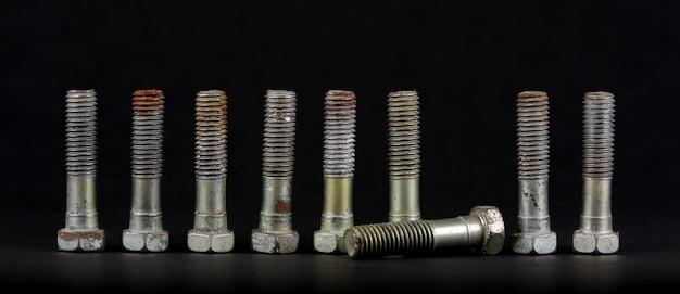 Dziewięć śrub z nakrętkami w rzędzie. jeden obiekt leży poniżej.