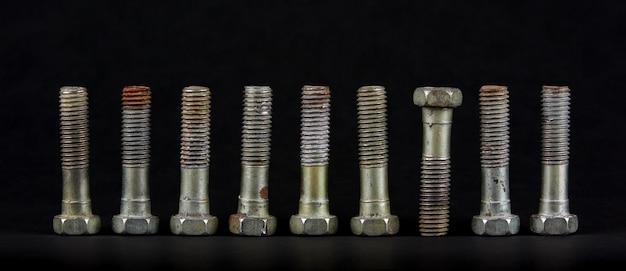 Dziewięć śrub z nakrętkami w rzędzie. jeden przedmiot różni się od pozostałych położeniem. część jest do góry nogami.