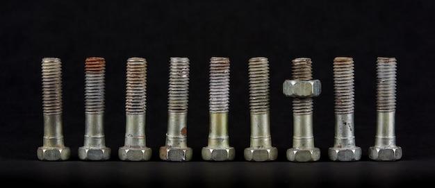 Dziewięć śrub z nakrętkami w rzędzie. jeden przedmiot różni się od pozostałych położeniem. część ma nakrętkę.