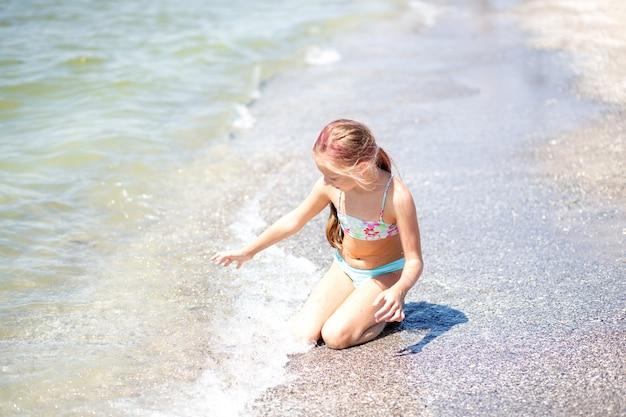 Dziewięcioletnia dziewczynka z różowymi długimi włosami siedzi na piaszczystej plaży w pobliżu wody w kostiumie kąpielowym i bawi się wodą