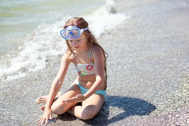 Dziewięcioletnia dziewczynka z różowymi długimi włosami siedzi na piaszczystej plaży w pobliżu wody z okularami do pływania na głowie i bawi się ze spuszczonymi oczami