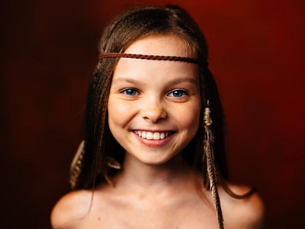 Dzika dziewczyna z piórkiem we włosach uśmiech luźnych włosów indyjskiej kultury.