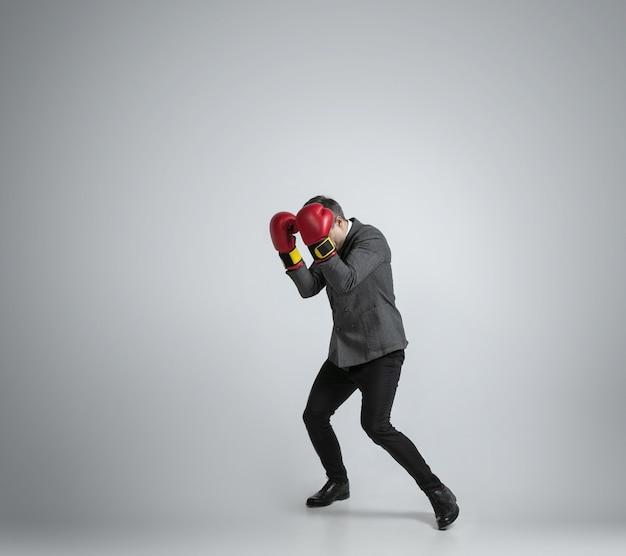 Dziki i młody. kaukaski mężczyzna w biurowych ubraniach bokserskich z dwoma czerwonymi rękawiczkami na szarym tle