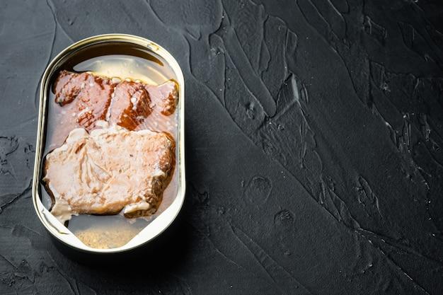 Dziki łosoś z alaski zestaw konserw wędzonych ryb, w puszce, na czarnym tle, z copyspace i miejscem na tekst