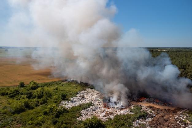 Dziki pożar na wysypisku śmieci. biało-szary dym z płonących śmieci na miejskim wysypisku