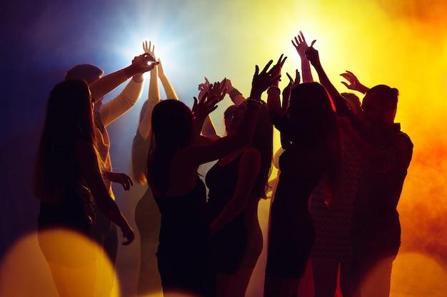 Dziki. tłum ludzi w sylwetce podnosi ręce na parkiecie na neonowym tle. życie nocne, klub, muzyka, taniec, ruch, młodzież. żółto-niebieskie kolory i poruszające dziewczyny i chłopcy.