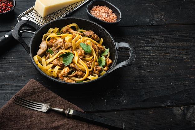 Dziki zając z warzywami w sosie z białego wina makaron tagliatelle lub zestaw pappardelle, na patelni żeliwnej lub garnku, na czarnym drewnianym stole
