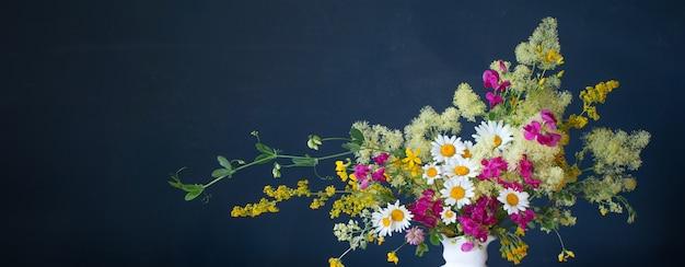 Dzikie kwiaty w białym wazonie na ciemnoniebieskim tle