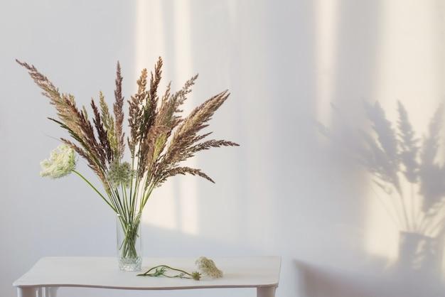 Dzikie rośliny traw w szklanym wazonie w słońcu w białym wnętrzu