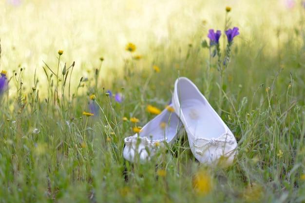 Dzikie tło z nieostre kwiaty pimaveral i białe buty dziewczyny do komunii