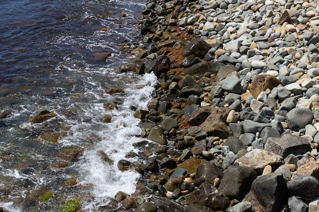 Dzikie wybrzeże z kamykami i falami. pejzaż morski.