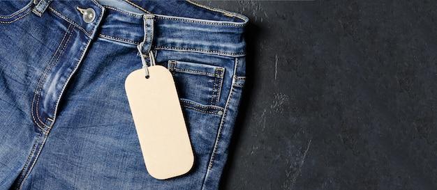Dżinsowa. niebiescy dżinsy na czarnym tle. etykieta do pisania tekstu. skopiuj miejsce pojęcie sprzedaży towarów w sklepie.
