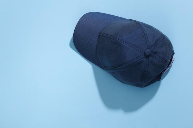 Dżinsy niebieska czapka na niebieskim jasnym tle z głębokim cieniem.