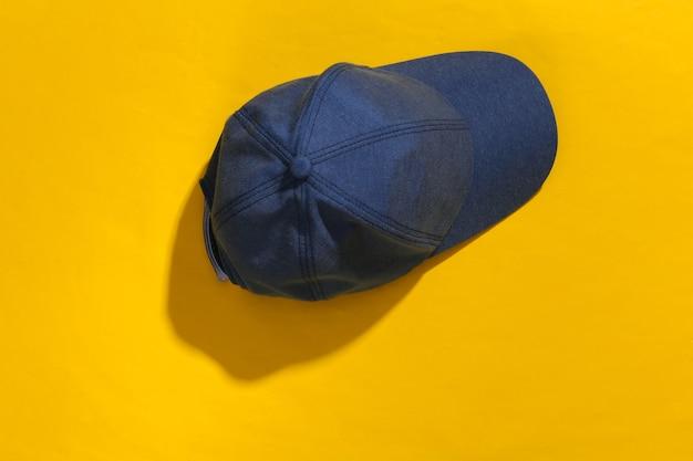 Dżinsy niebieska czapka na żółtym jasnym tle z głębokim cieniem.