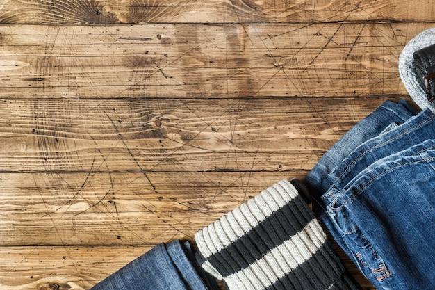Dżinsy ubrania i akcesoria na brązowej powierzchni drewna